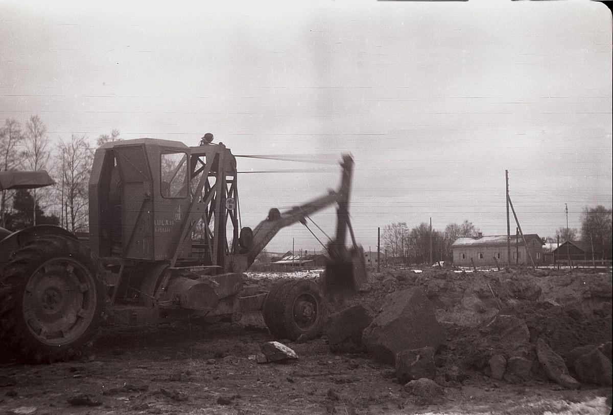 1957 grävs grunden för den nya Centralskolan. Grävmaskinen tillhör Olof och Helge Holm, Ragnar Jossandt och Runar Storsjö. I bakgrunden syns Storhannus gård.