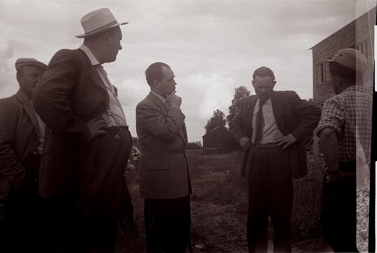Kommunens män diskuterar bygget av Centralskolan med byggarna. I bakgrunden syns Jakob af Hällströms häbbre.