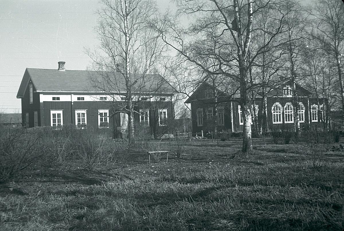 Till vänster lärarbostaden, som år 1879 byggdes till Lappfjärds bys första folkskola. När den nya skolbyggnaden till höger byggdes 1893, så renoverades den gamla skolan till två bostäder. Den ena var ämnad åt läraren och den andra skulle den kommande lärarinnan kunna bo i.
