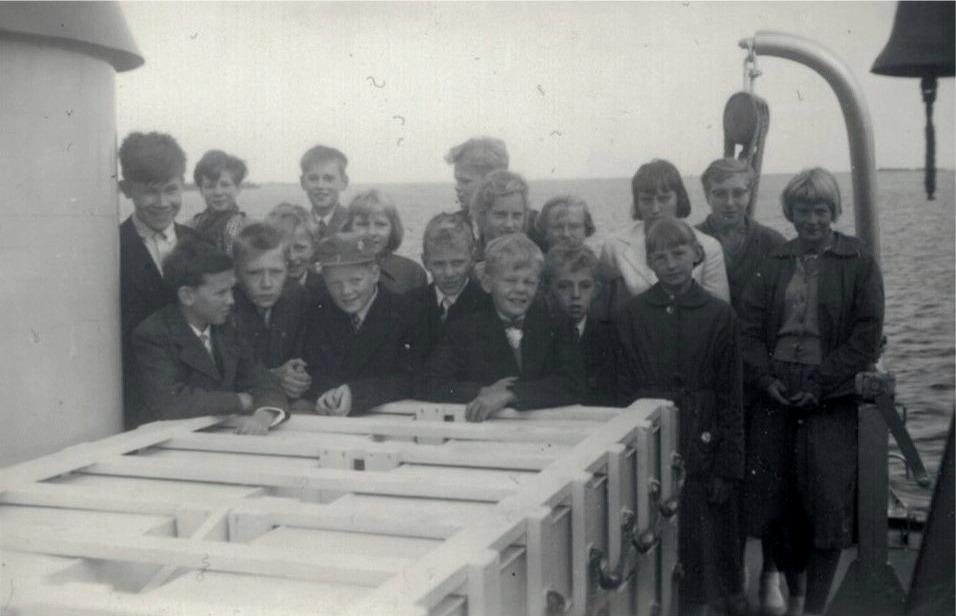 En upplevelse att få åka färja över till Replot år 1959. Från vänster Torolf Söderlund, Kaj Rosenback nere, Marita Nissander där bak, Bengt Mangs och en okänd nere, i bakgrunden Bo Göran Ingves, nere med mössan Stig Björknäs och bakom honom Berit Mangs. Följande är Stig Brandt. Pojken i bakgrunden som tittar åt sidan är Bo Göran Södergård och framför honom står af Hällström och Bo Söderlund. Följande är Marlene Granskog som står framför en okänd pojke. Bredvid Marlene står Berit Lillgäls framför en okänd flicka. Längst till höger står Maj-Lis Lillmangs och Britta Bergkulla.