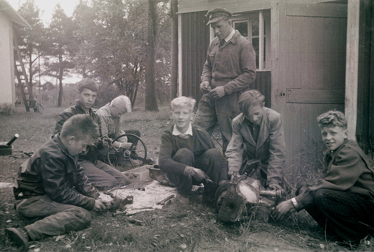 Läraren Alvar Hirsimäki framför centralskolans uthus visar åt eleverna hur en motor fungerar. Från vänster Yngve Aspås, Seppo Lehtimäki, Fride Grahn, Rolf Rosenholm, okänd och till höger Stig Aspås.