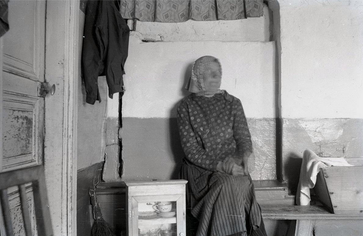 """Gammal kvinna sitter på """"spisbre"""" i sitt enkla hem."""