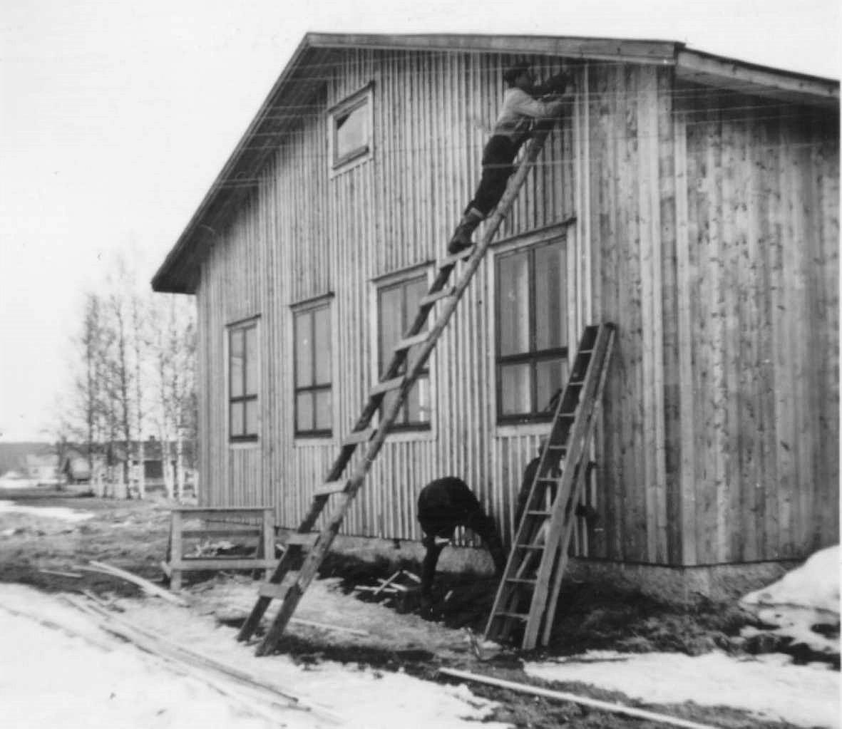 """Gaveln till serveringsrummet """"ribbas"""" , alltså ribbor spikas ovanpå brädfodringen. Klemets Erik Anders gård syns till vänster och riktigt långt bort står Åke Backlunds gård på A-sidon."""