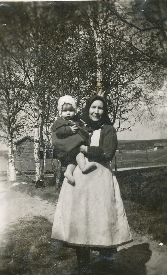 Selma Granholm på gården med barnbarnet Inger i famnen, år 1943.