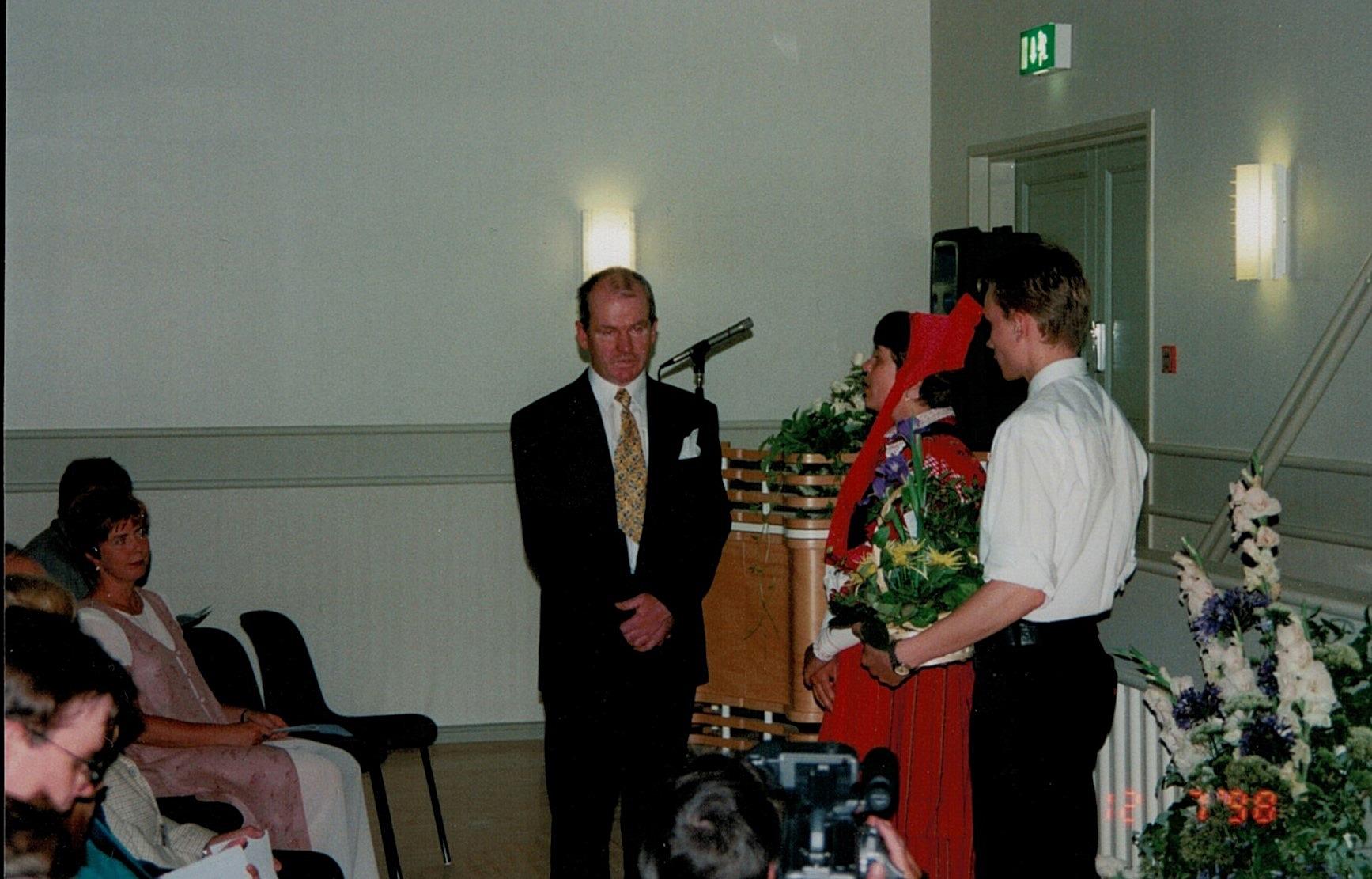 Kurt Backlund som under byggnadstiden fungerat som byggnadskommitténs ordförande blir uppvaktad med blommor på invigningsfesten av Åsa Ekman och Niklas Rosengren.