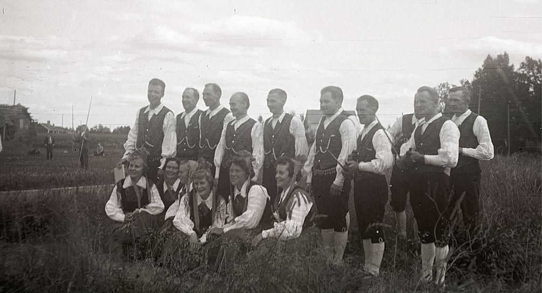 Sju par folkdansare och fyra spelmän på idrottsplan i Lappfjärd. Från vänster Venzel och Elin Smith, Lars och Gunvor Lillhannus, Nils och Ann-Lis Björklund, Eric och Irma Stens, Magnus och Gunnevi Åstrand, Ole (skymd) och Greta Åhlqvist och Helge och Maj-Britt Holm. Spelmännen är Torsten Pärus, Torsten Nyholm (skymd), Valter Enlund och Otto Fröberg.
