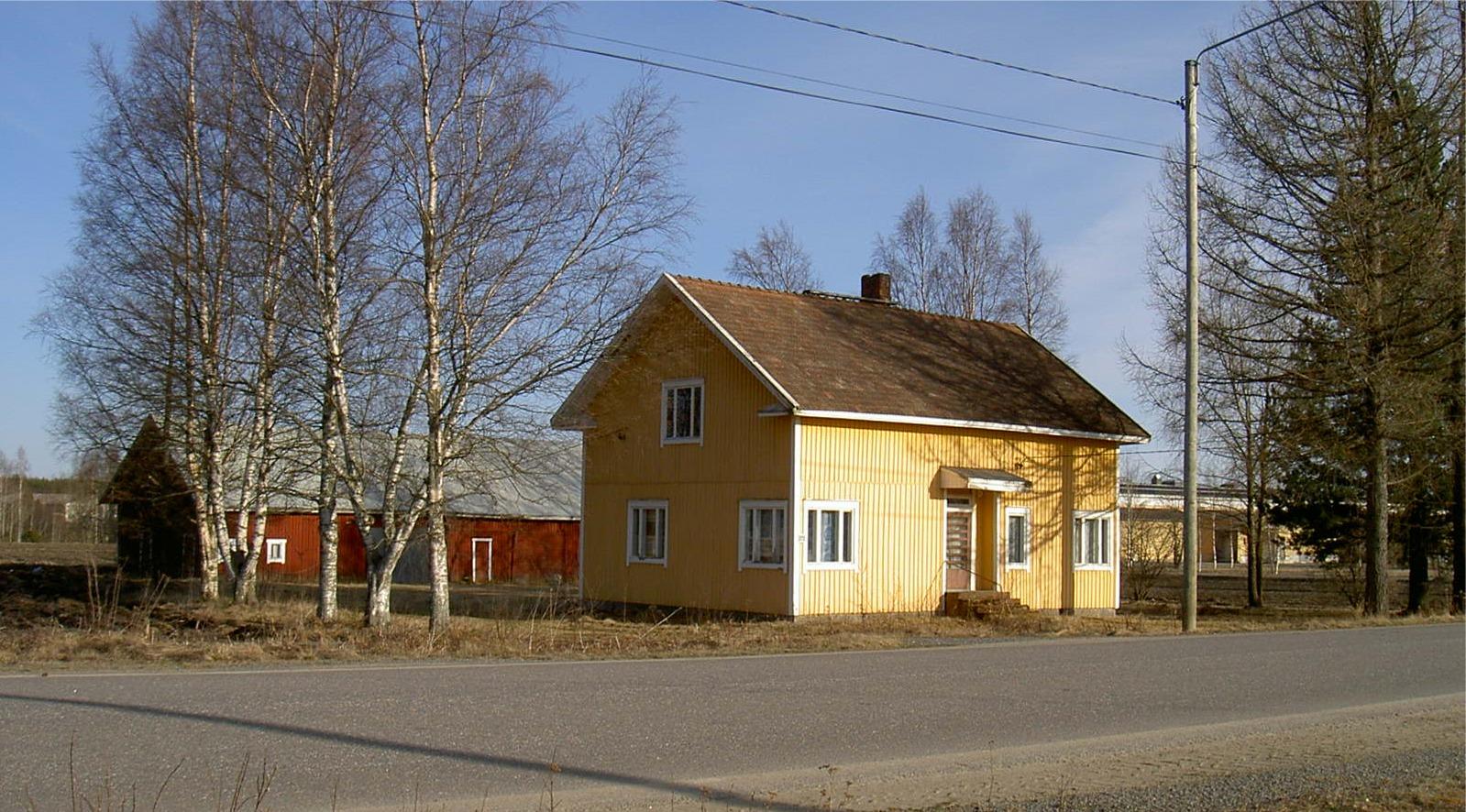 Eskil Rosenbacks gård fotograferad från norr år 2003. Till vänster om uthuset skymtar växthusen på Mellanå Plant och i högra kanten syns Estrellas fabriksbyggnader.