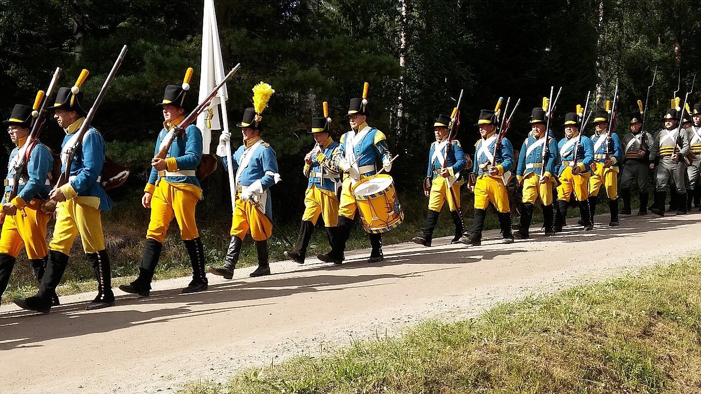 """Mitt i bild en trumslagare i Oravais historiska förening år 2018. På 1700- talet skulle trumslagaren utrustas med 2 svarta halsdukar, 2 blåa klädesrockar, 2 gula västar, 2 gula """"böxor"""" och 2 hattar."""