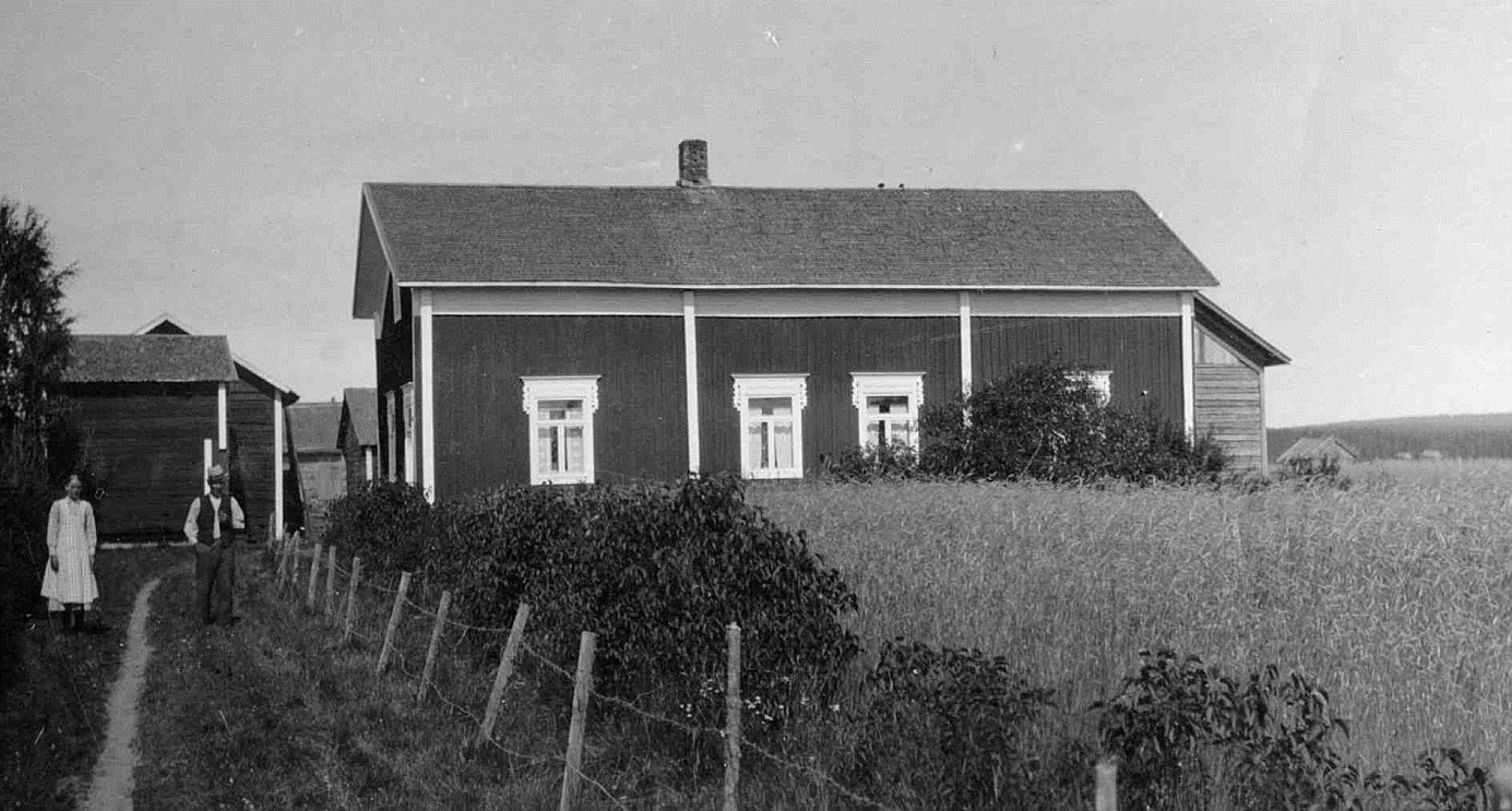 Den här gården flyttade Valentin Rosenback från Likvagnsjäälon mittemot folkskolan, upp till Åbackan under storskiftet 1900-1912. På bilden står Valentin tillsammans med dottern Elin Rosenback. Gården revs 1951 och stockarna användes på nytt då sonen Eskil Rosenback byggde den nya gården på andra sidan Åbackvägen.