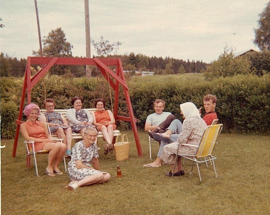 Släktträff hemma hos fröken Elin Rosenback, som sitter på gräsmattan. Från vänster Birgit Rosenback, Ines Rosenback, Anna Sonntag, Inger Wiklund, Börje Wiklund, Selma Rosenback och Roy Rosenback.