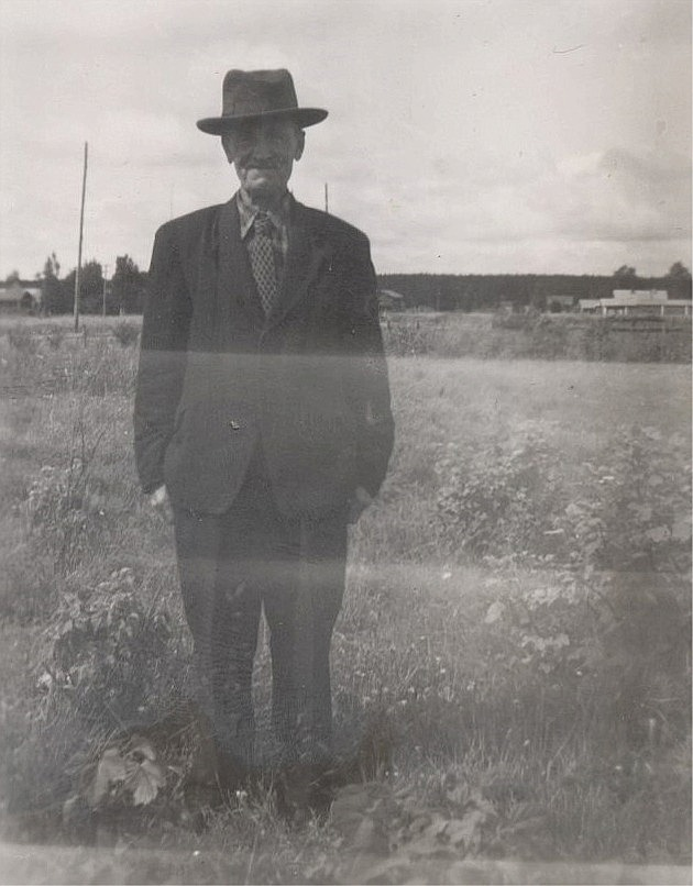 Erland Grönroos (1882-1963) står nära Lillsjövägen, med gårdarna i Palon i bakgrunden.