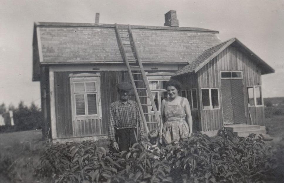 Någon gång runt 1950 flyttade ingången från gaveln i norra ändan till långsidan mot öster. Här står Erland Grönroos tillsammans med sonhustrun Helga och lilla Ove framför gården.
