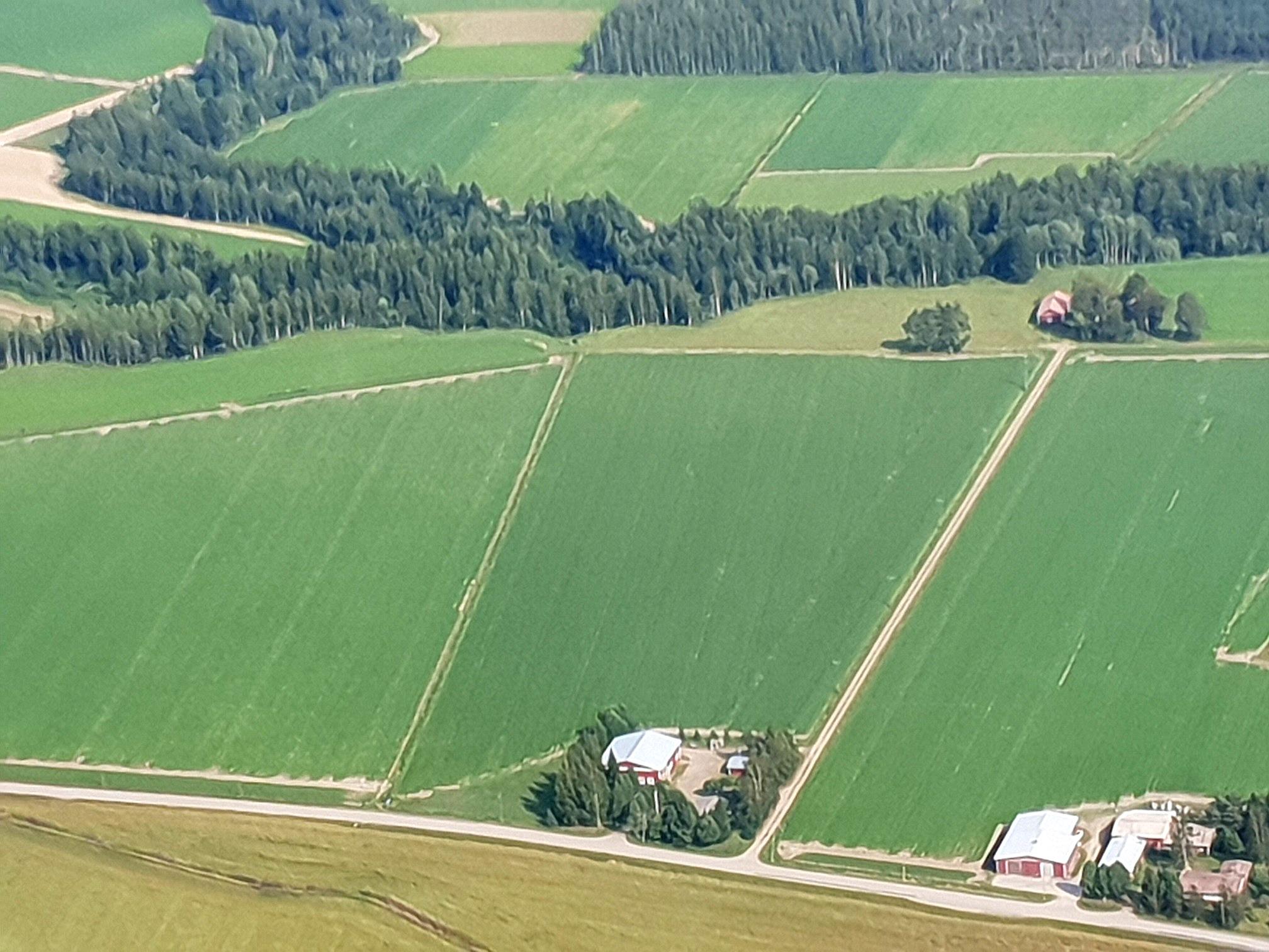 Här ser vi att åkrarna är stora på Åbackan och att det är långt mellan gårdarna. Uppe till höger bakom träden finns Lindfors gamla gård och nere i mitten finns Lindfors nya gård. Nere i högra hörnet syns Kauko Santamäkis gårdsgrupp.