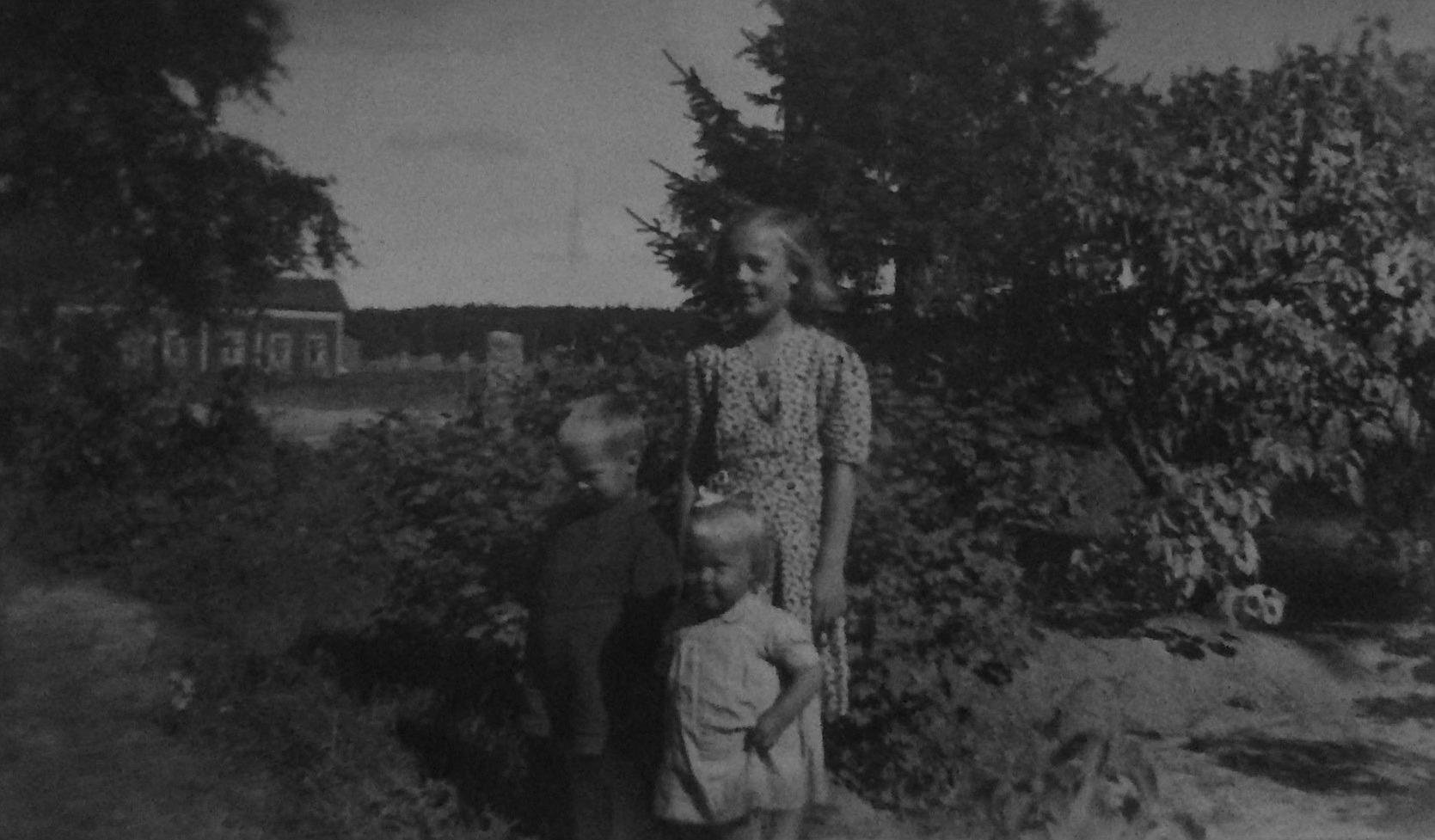 """Syskonen Jarl, Annel och Gun-Lis Grans i trädgården. I bakgrunden syns """"Roraas-Viktor"""" Rönnkvists gård."""