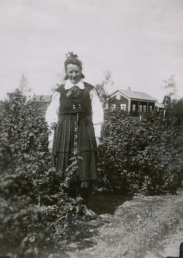Ines Wiklund, senare Rosenback iklädd Lappfjärds folkdräkt. I bakgrunden syns Valentin Rosenbacks bondgård.