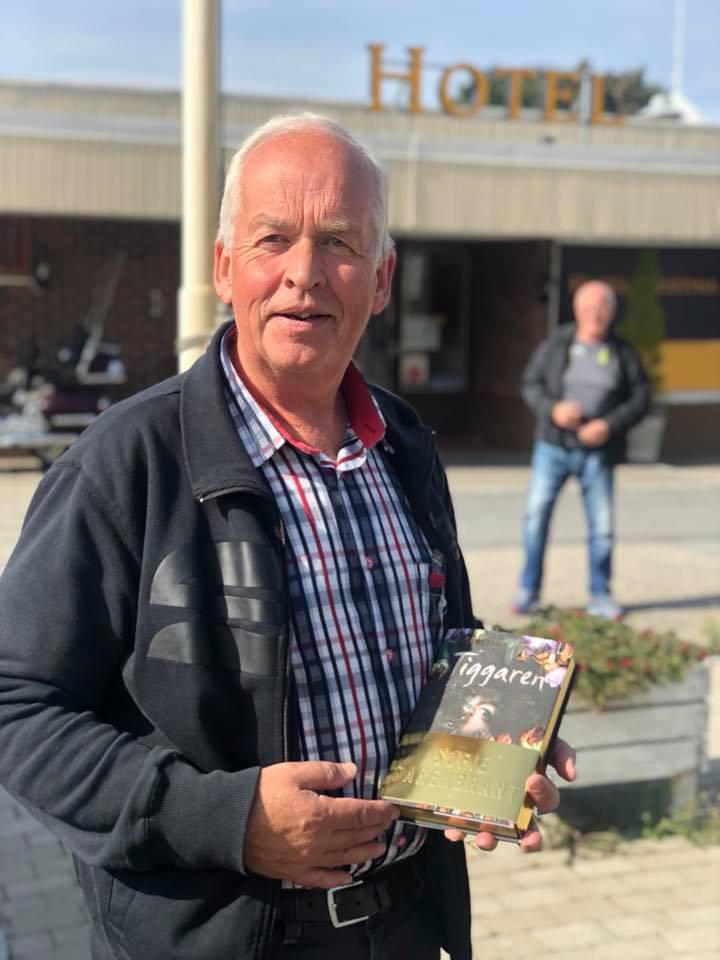 """Tommys fru Sofie Sarenbrant är en av Sveriges mest lästa författare och hon har sedan 2010 kommit ut med ungefär en bok varje år. Sedan 2012 skriver hon på heltid och hon har sålt långt över en miljon böcker, så huvudpersonen i flera av hennes deckare, Emma Sköld är välkänd för miljoner läsare. Som tack för guidningen i Dagsmark fick jag en signerad och numrerad bok av """"Tiggaren"""" som hon kom ut med 2016. I bakgrunden utanför Hotel Kristina står Roy och gör sig färdig för en dramatisk utfärd till hembyn Dagsmark."""