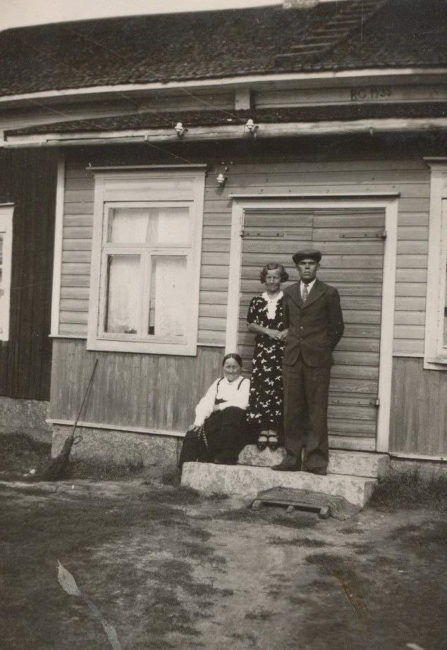 Signe och Lennart Grans står finklädda på trappan medan Signes mor Selma är klädd i folkdräkten. Under utskeftet står årtalet 1935 och det kan betyda det år då gården byggdes om och fick en ny stenfot.