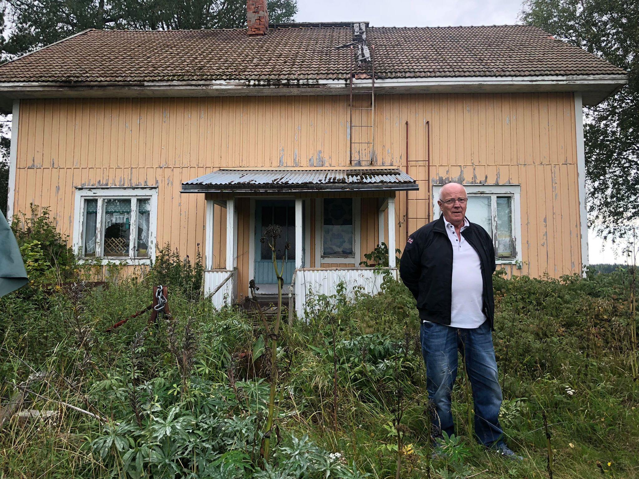 Roy Rosenback utanför den förefallna hemgården dit han flyttade som 6-åring och där han bodde i 10 år före han flyttade till Sverige.