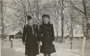 Här står Gerda Klåvus och Verna Agnäs i skolgrinden. I bakgrunden likvagnshuset, duvslaget och Lillsjös karamellfabrik till höger.